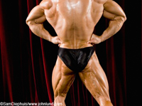 Picture of a man flexing his massive back muscles during a bodybuilding competition. The man has huge back and upper leg muscles. The man has his fists on his waist and the picture is cropped from knees to shoulders.